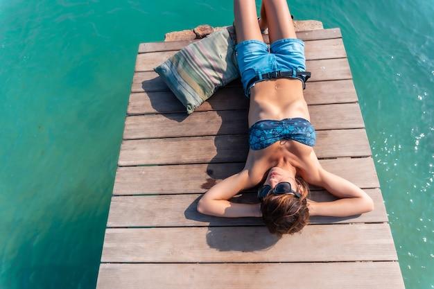 Une jeune femme pensive allongée profitant des vacances sur la passerelle en bois sur l'isla de lobos, au large de la côte nord de l'île de fuerteventura, îles canaries. espagne