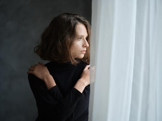 Jeune femme pensive aux cheveux bouclés près de la fenêtre