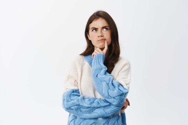 Jeune femme pensive ayant des doutes, quelque chose qui cloche, fronçant les sourcils et touchant la lèvre tout en regardant pensivement dans le coin supérieur droit, se tenant méfiante contre le mur blanc