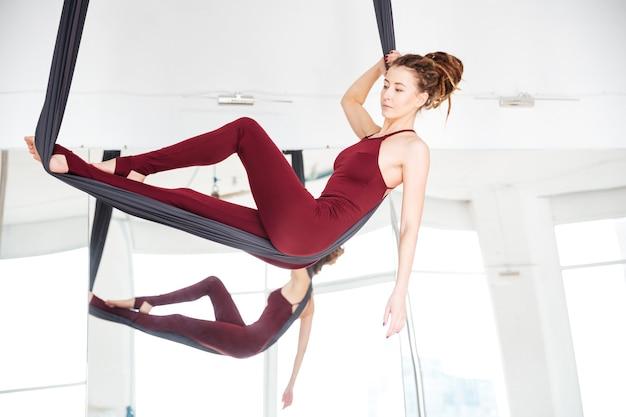 Jeune femme pensive faisant du yoga antigravité à l'aide d'un hamac sur le miroir