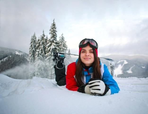 Jeune femme pensive en hiver dans la forêt enneigée au sommet des montagnes