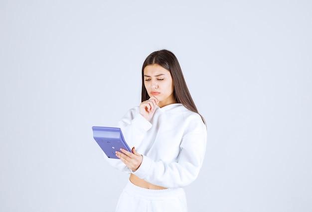 Jeune femme pensive regardant une calculatrice sur fond blanc-gris.