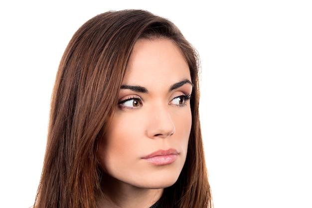 Jeune femme pensive triste sur fond blanc