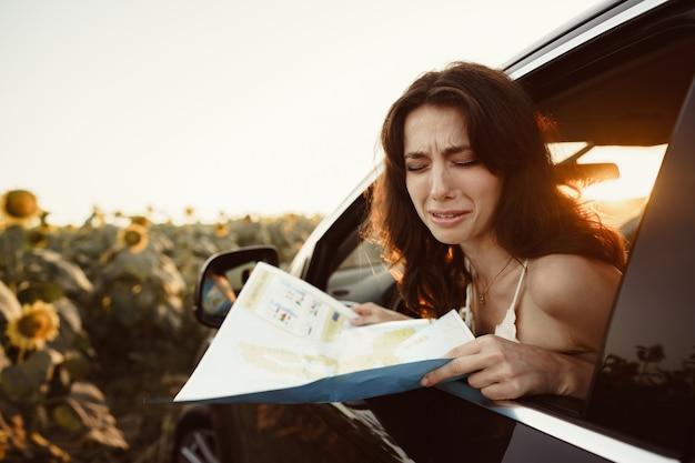 Jeune femme perdue assise dans sa voiture à la campagne et regardant la carte