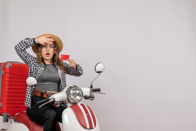 Jeune femme perplexe sur cyclomoteur holding card sur gray