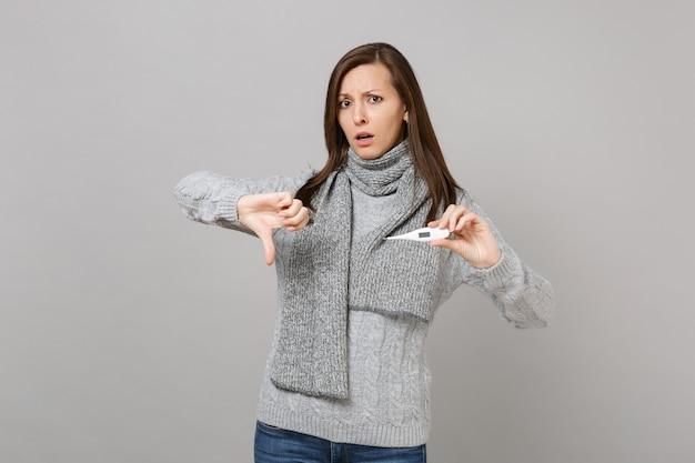 Jeune femme perplexe en écharpe pull gris montrant le pouce vers le bas, tenir le thermomètre isolé sur fond de mur gris. mode de vie sain, traitement des maladies malades, concept de saison froide. maquette de l'espace de copie.