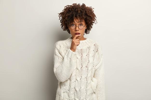 Une jeune femme perplexe à la peau sombre regarde nerveusement, écoute des informations importantes, ouvre la bouche de stupéfaction, porte des lunettes rondes, un pull blanc, pose à l'intérieur. concept d'expressions faciales humaines