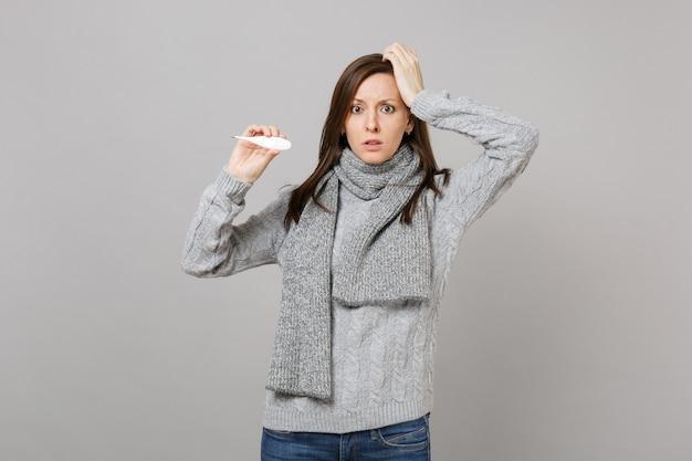 Jeune femme perplexe en pull gris, foulard mis la main sur le front, tenir le thermomètre isolé sur fond gris. mode de vie sain, traitement des maladies malades, concept de saison froide. maquette de l'espace de copie.