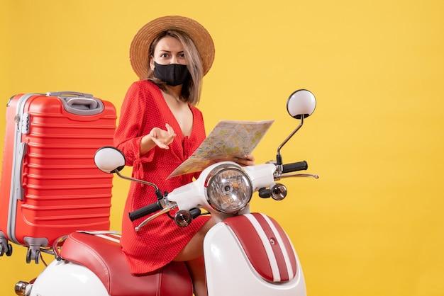Jeune femme perplexe en robe rouge sur cyclomoteur holding map