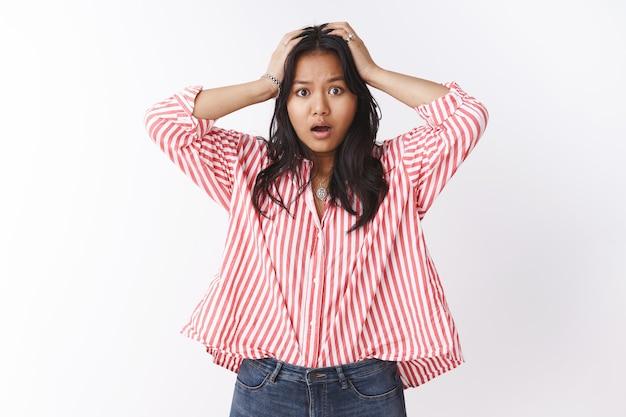 Jeune femme perplexe et troublée se sentant confuse et anxieuse face à une situation gênante saisissant la tête avec les deux mains dans le désespoir et l'inquiétude haletant, l'air inutile devant la caméra sur un mur blanc