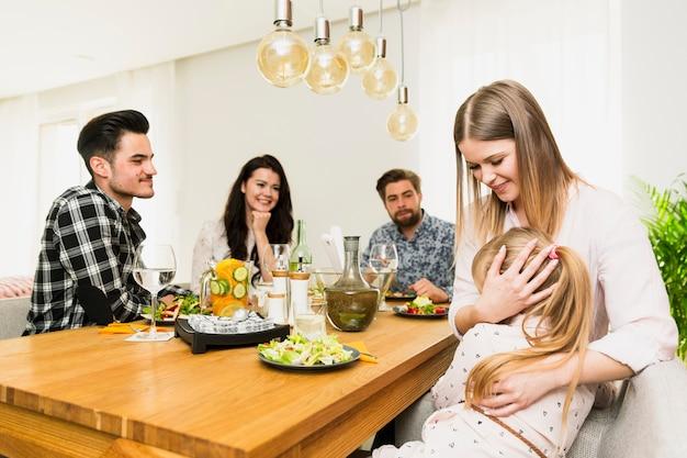 Jeune femme avec petite fille et amis assis à table