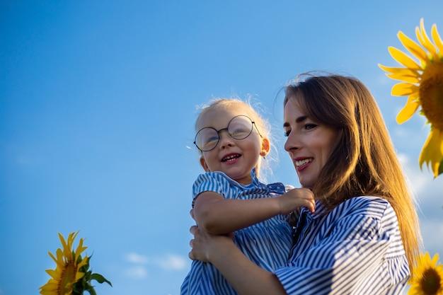 Jeune femme et une petite fille dans ses bras sur un champ de tournesol. maman avec l'enfant.