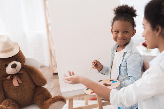 Jeune femme et petite fille dessiner ensemble.
