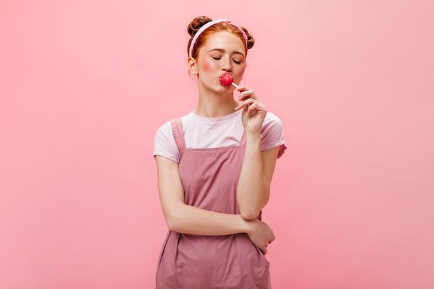 Jeune femme avec des petits pains vêtue d'une robe rose mange une sucette sur fond isolé.