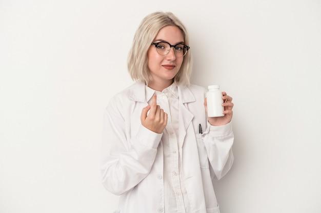 Jeune femme pharmacienne tenant des pilules isolées sur fond blanc pointant du doigt vers vous comme si vous vous invitiez à vous rapprocher.
