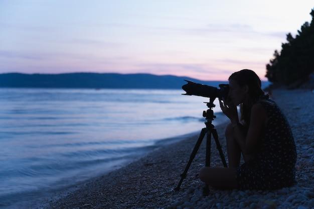 Jeune femme photographe assise sur une plage de galets le soir avec son appareil photo sur trépied prêt à photographier la mer et le paysage du soir.
