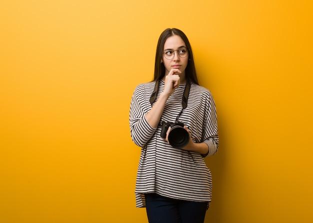 Jeune femme photographe doutant et confus