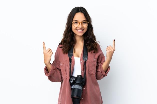 Jeune femme photographe sur fond blanc isolé pointant vers une excellente idée