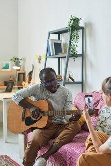 Jeune femme photographiant un jeune homme sur un téléphone portable pendant qu'il joue de la guitare à la maison
