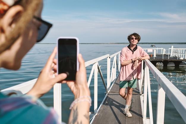 Jeune femme photographiant son beau petit ami élégant dans des lunettes de soleil posant sur la jetée
