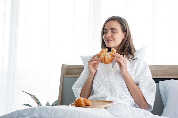 Jeune femme en pijama mange du pain après mon réveil le matin.