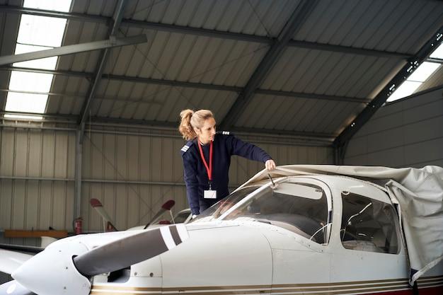 Jeune femme pilote découvrant des avions légers avec couvercle de protection dans le hangar