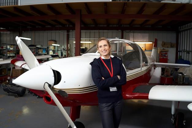 Jeune femme pilote posant souriant devant son avion à l'intérieur du hangar