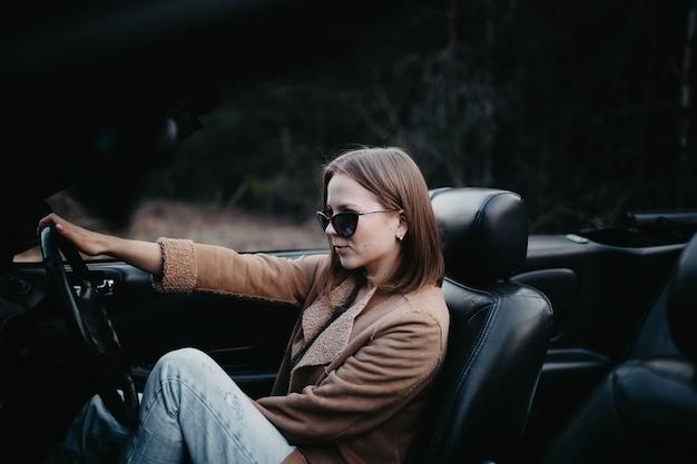 Jeune femme pilote en voiture décapotable en été