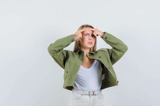 Jeune femme pinçant son bouton en veste, chemisier et à l'air irrité. vue de face.