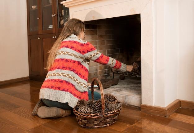 Jeune femme plaçant une pomme de pin dans la cheminée