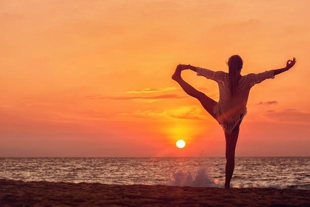 Jeune femme sur la plage fait un asana sur l'équilibre, natarajasana