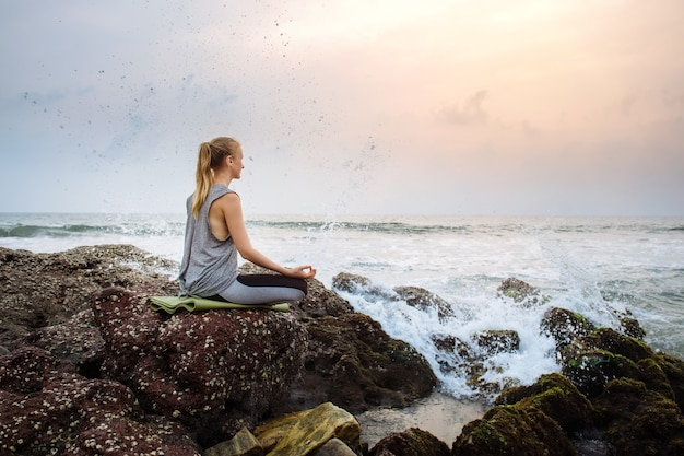 Jeune femme sur la plage pratique le yoga au bord de la mer pendant le coucher du soleil