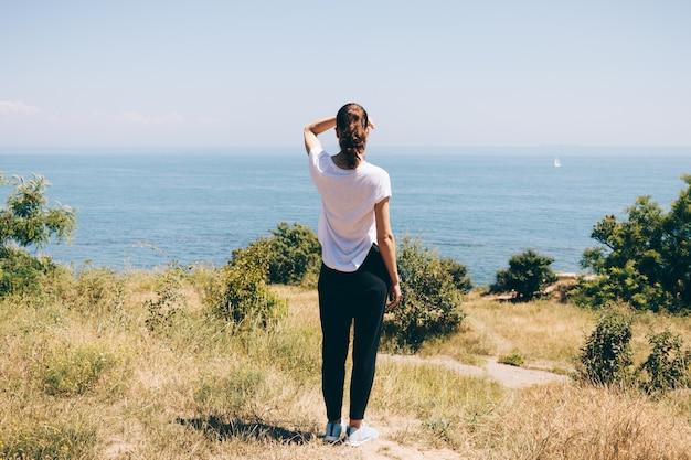 Jeune femme sur la plage en regardant la mer