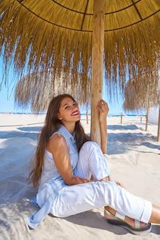 Jeune femme sur une plage sous un parasol