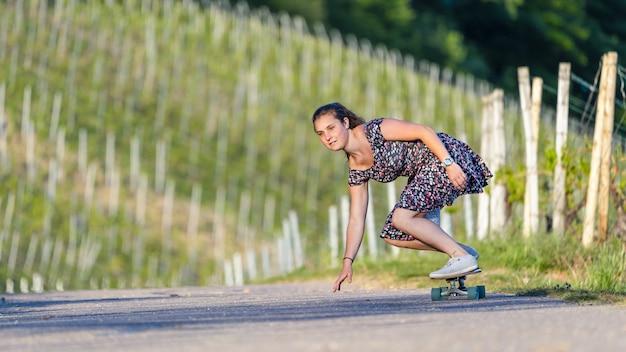 Jeune femme de la planche à roulettes sur une route vide entourée de verdure