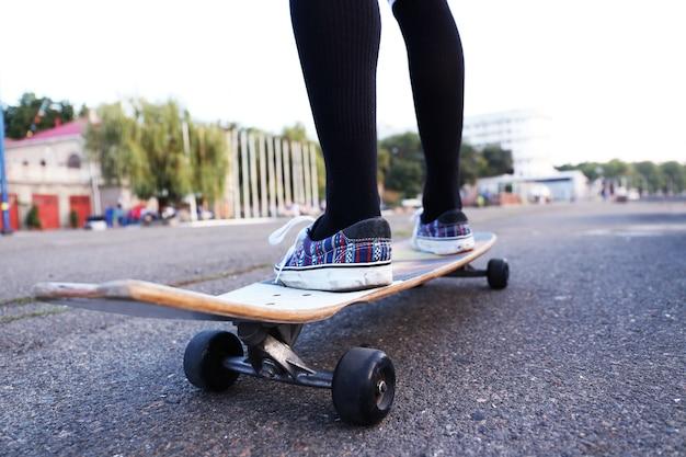 Jeune femme avec planche à roulettes sur la route