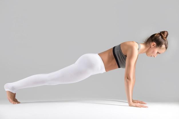 Jeune femme à plank pose, fond de studio gris