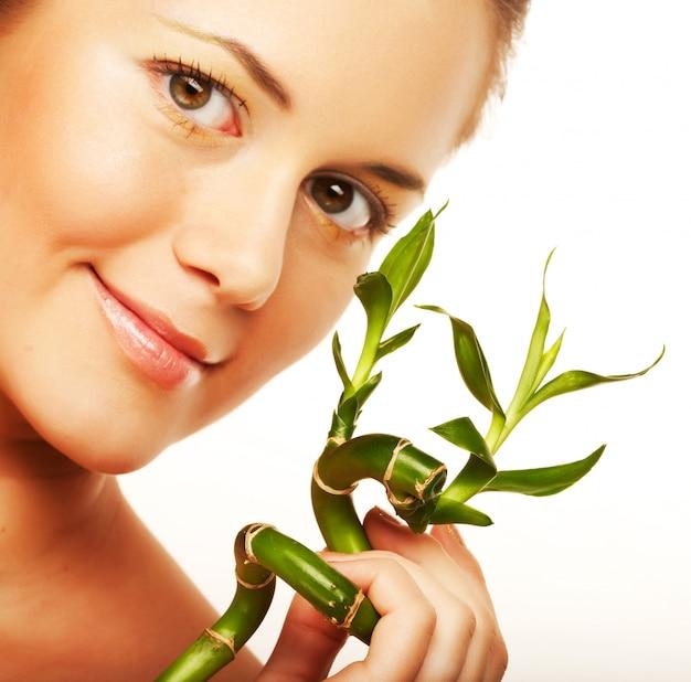 Jeune femme avec une plante de bambou