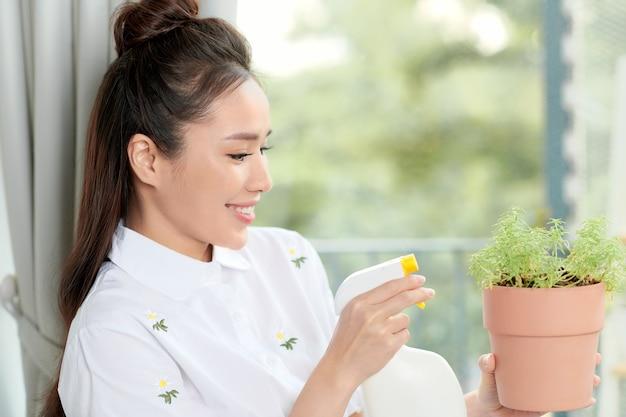 Jeune femme avec des plantes en pot sur un balcon de jardin. la floriculture est un passe-temps.
