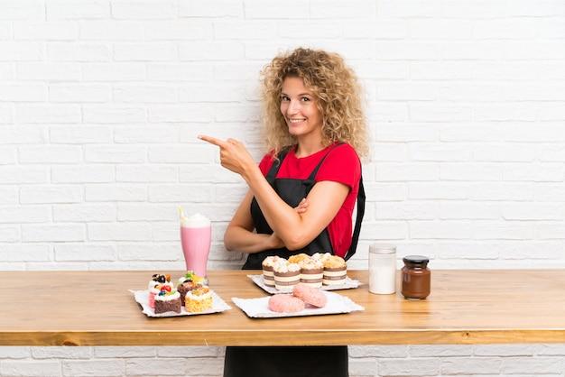 Jeune femme avec plein de mini gâteaux différents dans une table, pointant le doigt sur le côté