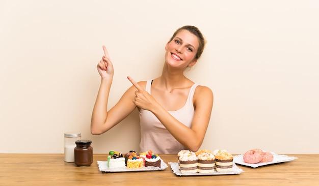 Jeune femme avec plein de mini gâteaux différents dans une table pointant avec l'index une bonne idée