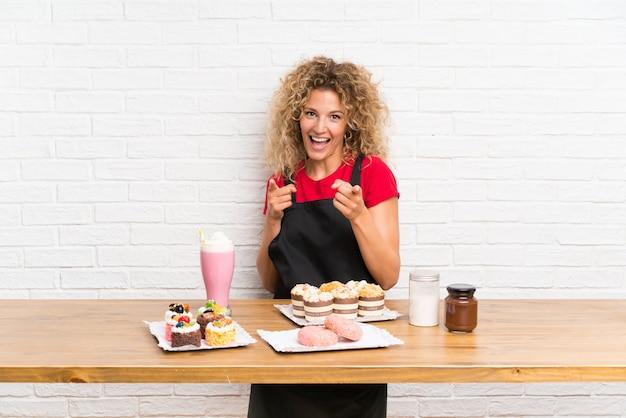 Jeune femme avec plein de mini gâteaux différents dans une table pointe le doigt vers vous