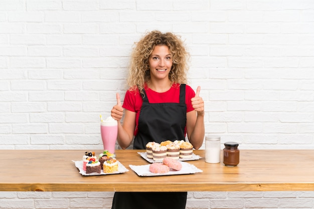 Jeune femme avec plein de mini gâteaux différents dans un tableau donnant un geste du pouce levé