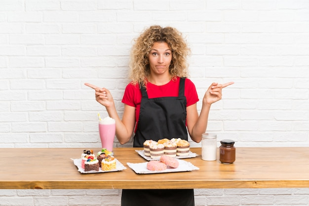 Jeune femme avec plein de mini gâteaux différents dans un tableau pointant vers les latérales ayant des doutes