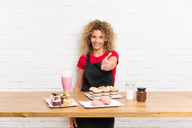 Jeune femme avec plein de mini gâteaux différents à la table après une bonne affaire