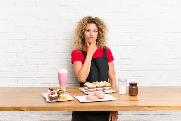 Jeune femme avec plein de mini gâteaux différents sur une table en pensant à une idée