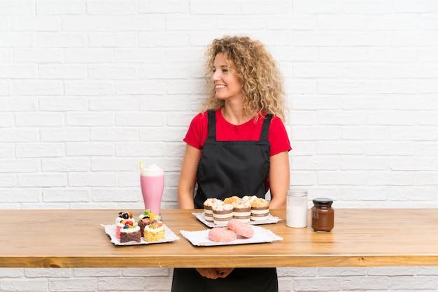 Jeune femme avec plein de mini gâteaux différents sur une table regardant de côté