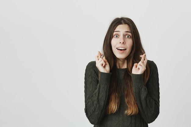 Une jeune femme pleine d'espoir attend de bonnes nouvelles avec les doigts croisés, fait un vœu