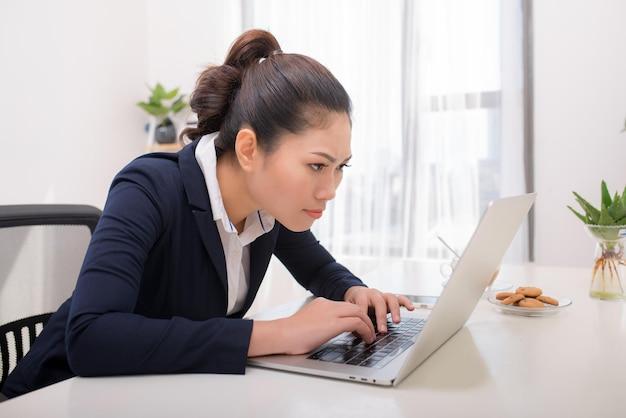 Jeune femme en pleine réflexion devant un ordinateur portable