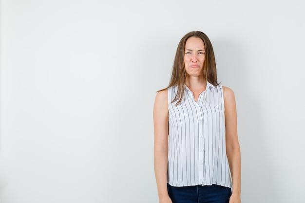 Jeune femme pleurant comme un enfant en t-shirt, jeans et à la recherche désespérée. vue de face.